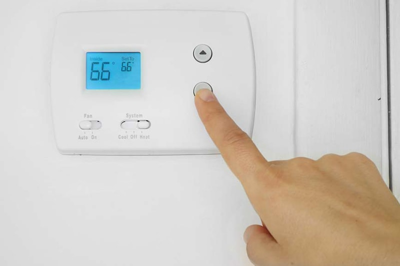 Is It Normal for My AC to Turn On and Off? Person's hand adjusting a wall mounted thermostat temperature
