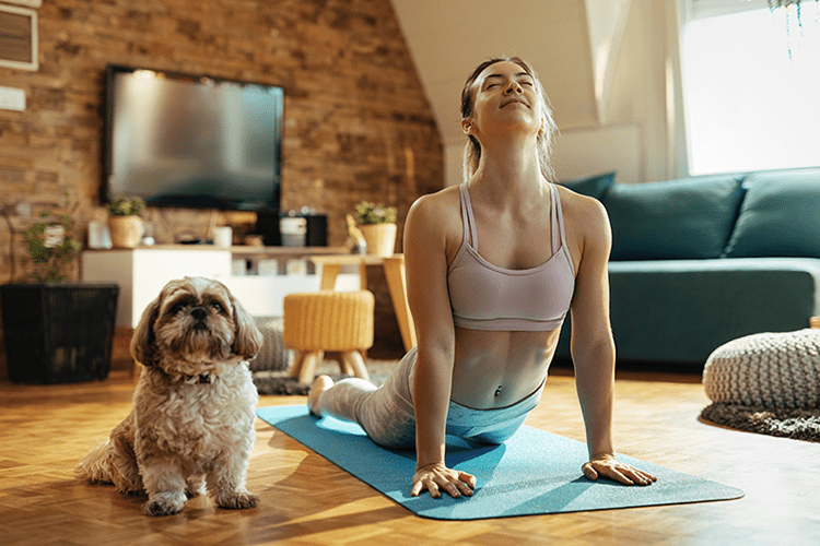 A young woman with her dog practicing yoga and enjoying good indoor air quality.